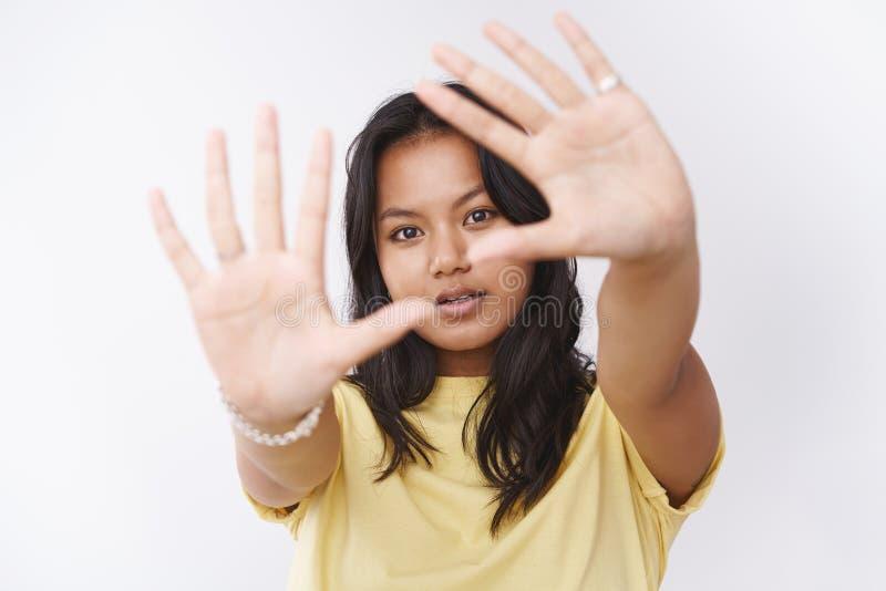 拉扯往照相机的黄色T恤杉的梦想的年轻可爱的马来西亚妇女棕榈看通过它注视 图库摄影