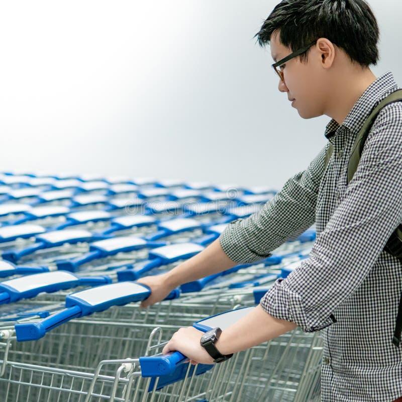 拉扯手推车的亚裔人在超级市场 免版税库存照片