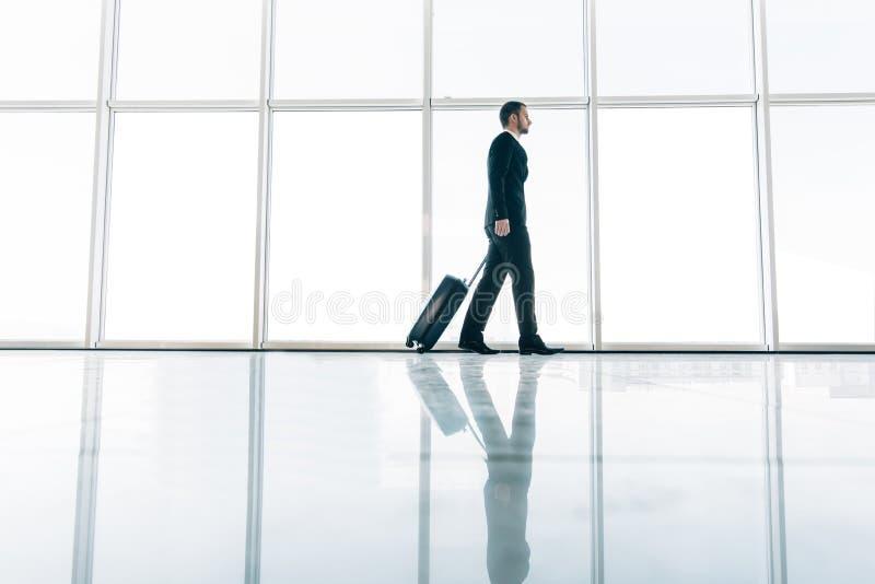 拉扯手提箱的年轻商人在现代机场终端 旅行的人或商人概念 商业对人立场手提箱行程负无法认出 免版税库存照片