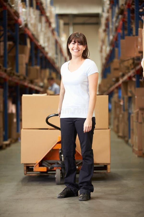 拉扯板台的女实业家在仓库里 免版税图库摄影