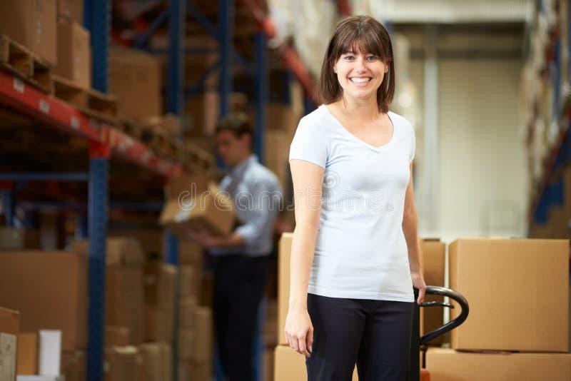 拉扯板台的女实业家在仓库里 库存照片