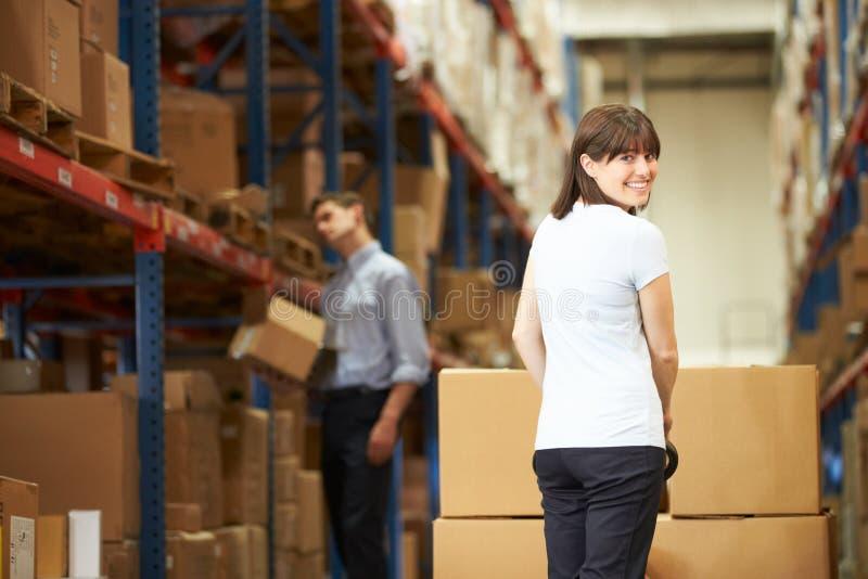 拉扯板台的女实业家在仓库里 免版税库存照片