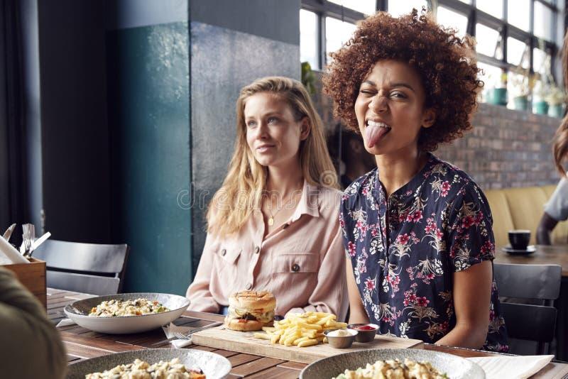 拉扯滑稽的面孔的妇女,她遇见饮料的朋友和食物在餐馆 图库摄影