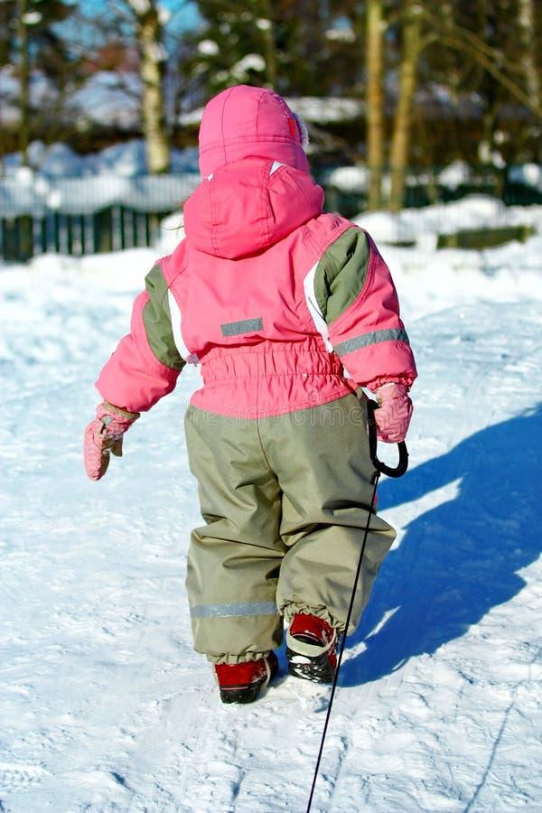 拉扯爬犁的总体的小女孩在冬天 库存图片