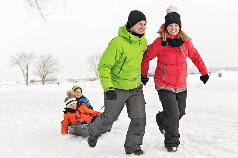 拉扯爬犁的逗人喜爱的家庭通过斯诺伊风景 免版税库存图片