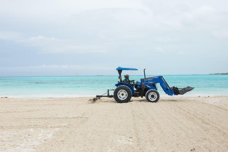 拉扯犁耙的拖拉机使海滩光滑 免版税图库摄影