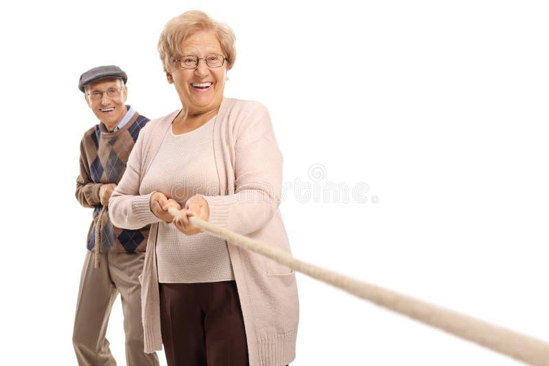 拉扯绳索的年长夫妇 免版税库存图片