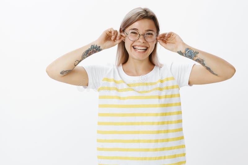 拉扯耳朵的生日女孩为每年她出生 逗人喜爱的黄色镶边T恤杉的正面漂亮的女人和 免版税库存照片