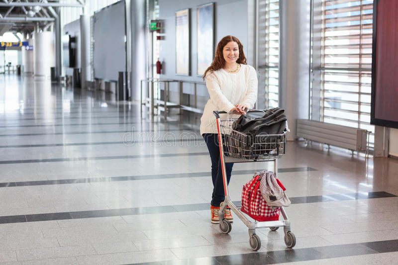 拉扯行李推车的少妇在机场 库存照片