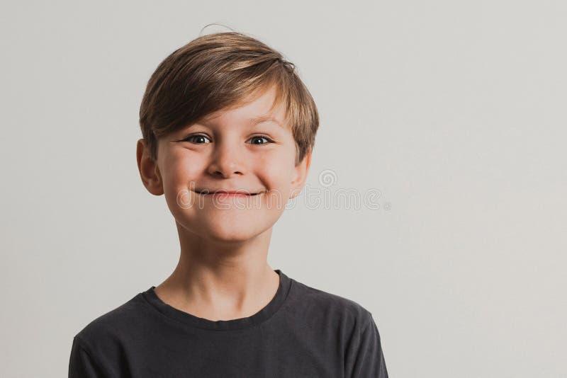 拉扯面孔的逗人喜爱的男孩画象 免版税库存图片