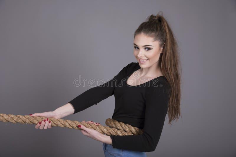 拉扯绳索的可爱的女孩 库存图片