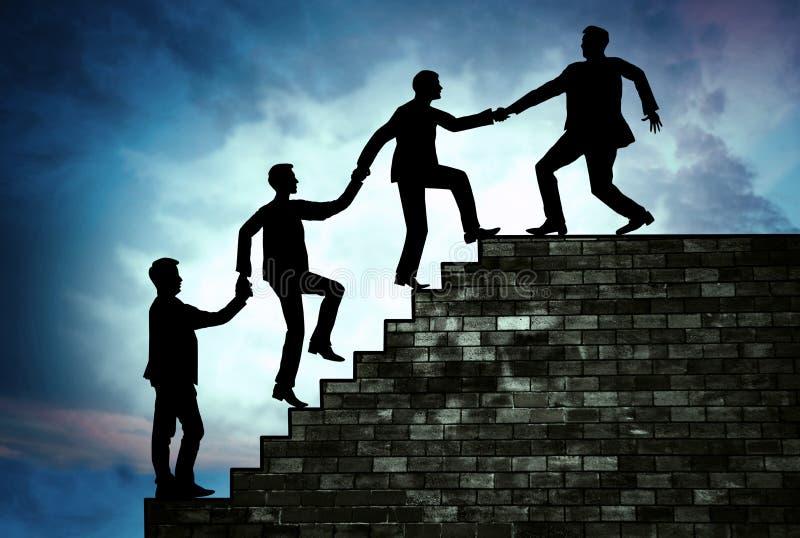 拉扯他的工作者的团队负责人对台阶的上面, suppor 免版税图库摄影