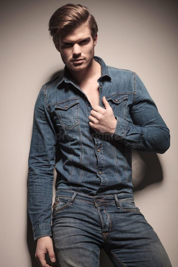 拉扯他的衬衣的可爱的年轻时尚人 库存照片