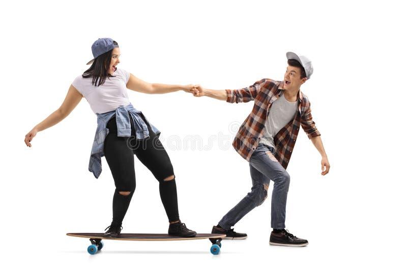拉扯longboard的十几岁的男孩一个十几岁的女孩 图库摄影