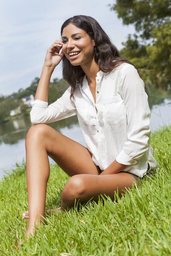 拉提纳妇女女孩坐草由湖在夏天 免版税图库摄影