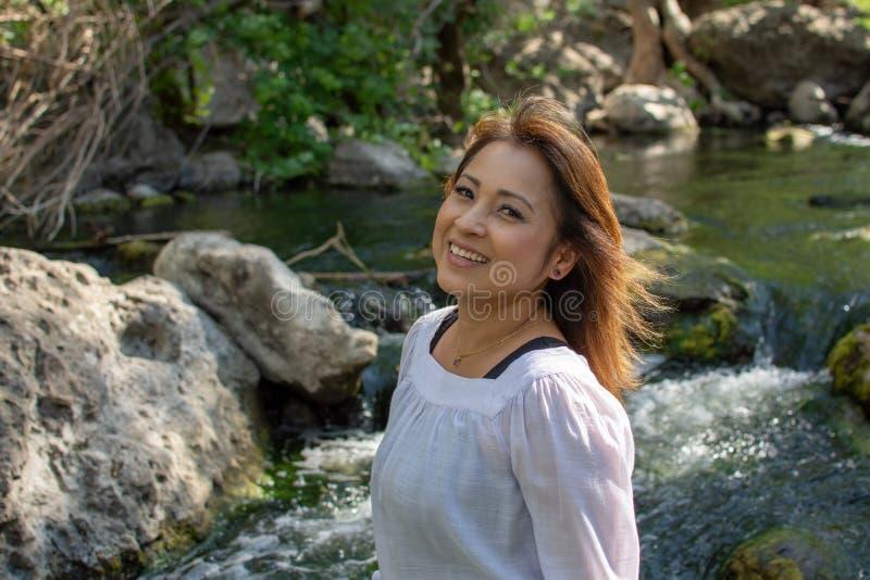拉提纳妇女微笑的身分在与发光的头发的树荫下在与瀑布的一条小河在背景中 免版税库存图片