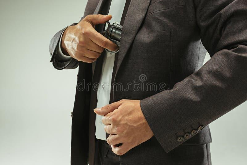 拉枪的商人从口袋里面 免版税库存图片