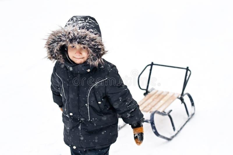 拉爬犁的冬天诉讼的新男孩 免版税库存图片
