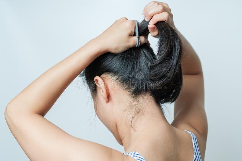拉紧头发,生活方式概念的妇女背面图  库存图片