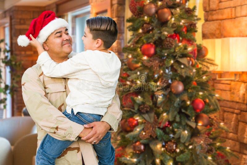 拉美裔戴圣诞老人帽子的武力战士拥抱儿子 免版税库存照片