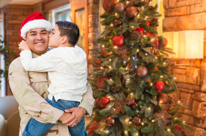 拉美裔戴圣诞老人帽子的武力战士拥抱儿子 免版税库存图片