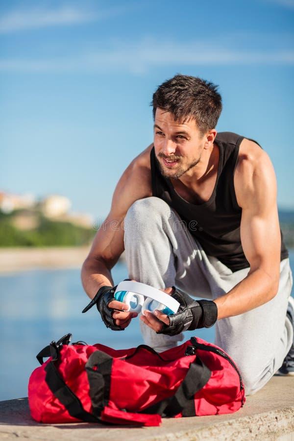拉耳机的坚定的年轻人从他的健身房袋子里面在锻炼前 免版税图库摄影