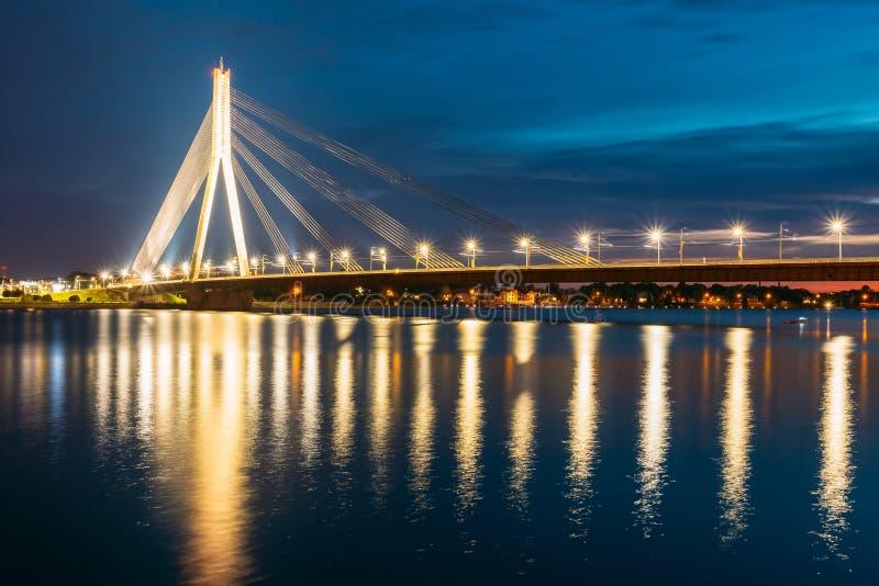 拉脱维亚里加 Vansu风景看法缆绳停留了在夜照明的桥梁在道加瓦河, 图库摄影