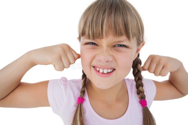 拉紧她的胳膊肌肉的小女孩 库存照片