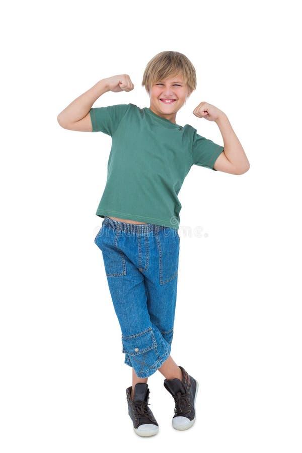 拉紧胳膊肌肉的愉快的白肤金发的男孩 免版税图库摄影