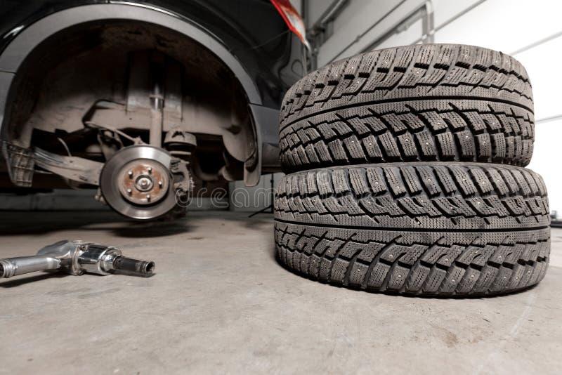 拉紧轮胎的气枪在一辆暂停的汽车闩上在一家汽车修理店 免版税图库摄影