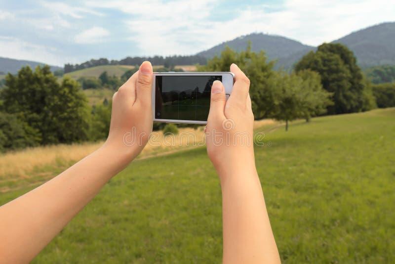 拍一张照片本质上少妇的手有智能手机的 免版税图库摄影