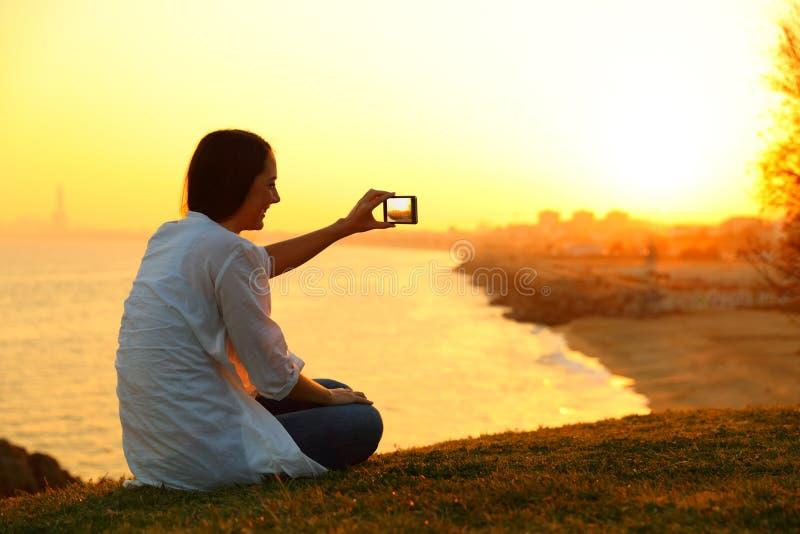 拍与一个巧妙的电话的妇女照片在日落 免版税库存图片