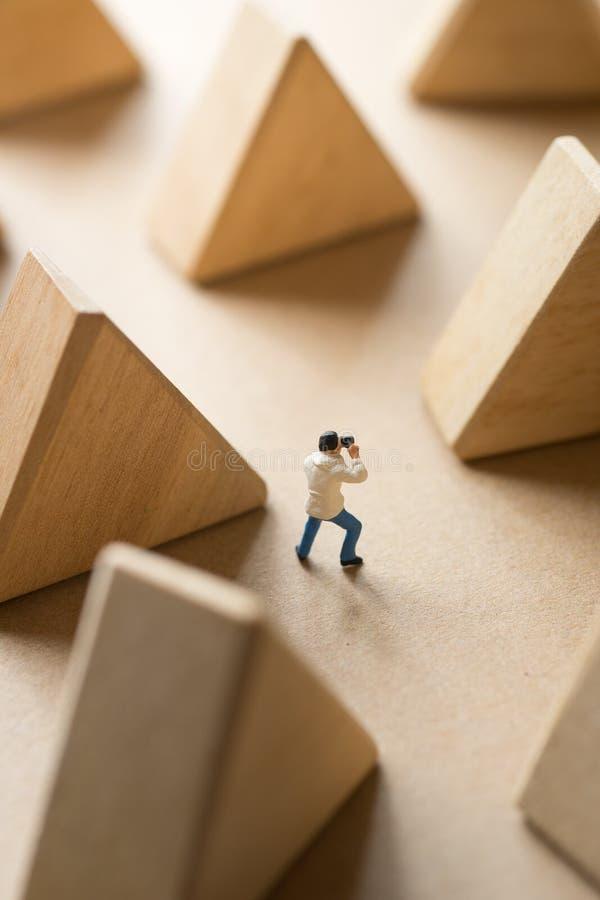 拍与三角木刻的微型人照片 库存图片