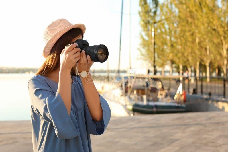 拍与专业照相机的年轻女性摄影师照片在码头 免版税图库摄影