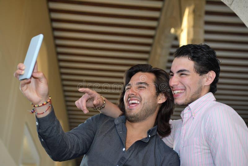 拍与他们的手机的愉快的快乐夫妇照片 免版税图库摄影