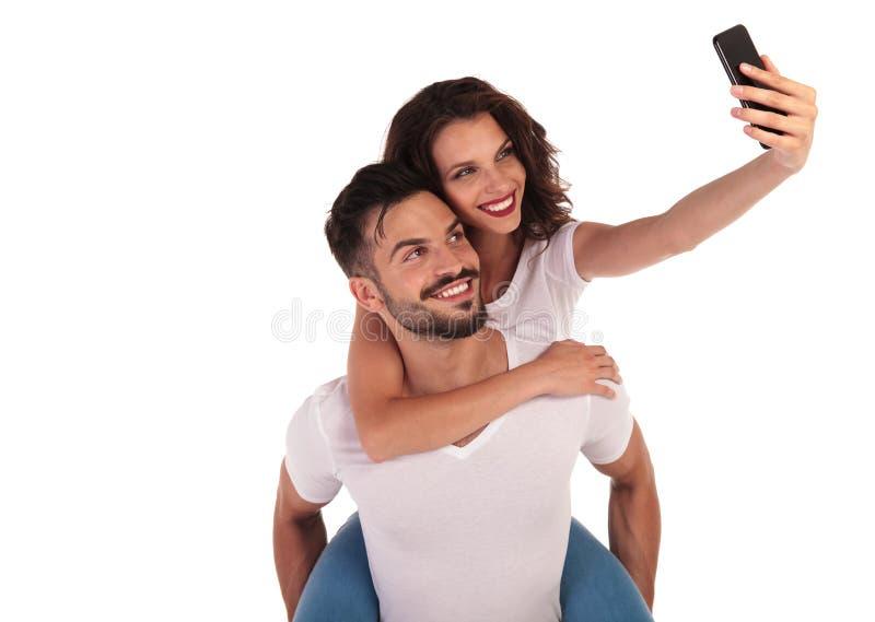 拍与他们的电话的偶然愉快的夫妇一张selfie照片 库存图片