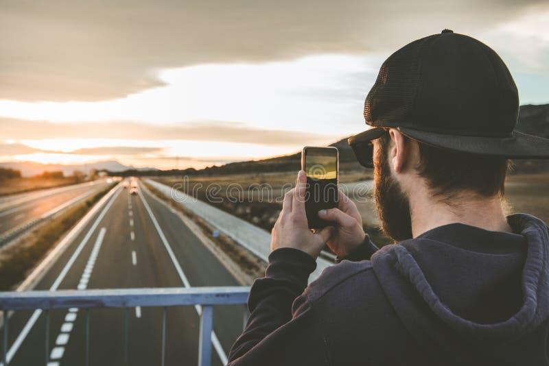 拍与他的手机的人一张照片在日落 照片样式人脉 库存照片
