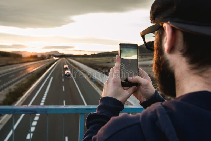 拍与他的手机的人一张照片在日落 照片样式人脉 免版税库存图片