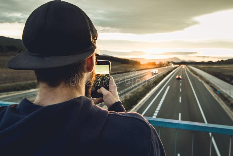 拍与他的手机的人一张照片在日落 照片样式人脉 免版税库存照片