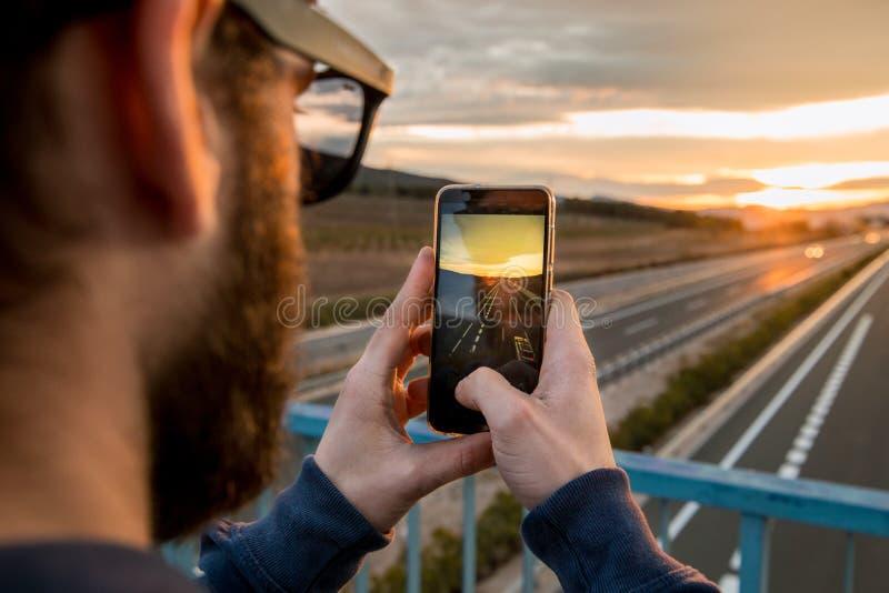 拍与他的手机的人一张照片在日落 照片样式人脉 图库摄影