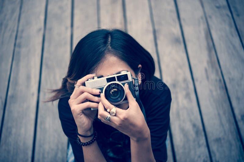 拍与减速火箭的影片照相机的行家妇女照片在木floorof城市公园,美丽的女孩在老照相机拍摄了 免版税库存图片