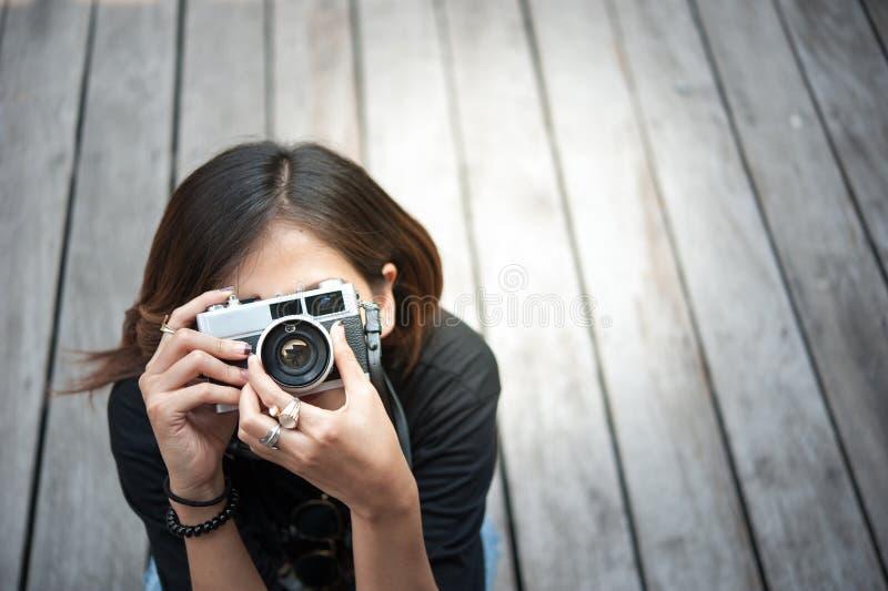 拍与减速火箭的影片照相机的行家妇女照片在木floorof城市公园,美丽的女孩在老照相机拍摄了 库存照片