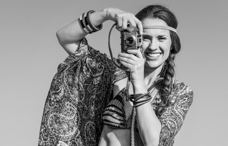 拍与减速火箭的照片照相机的时髦的吉普赛样式女孩照片 免版税库存照片
