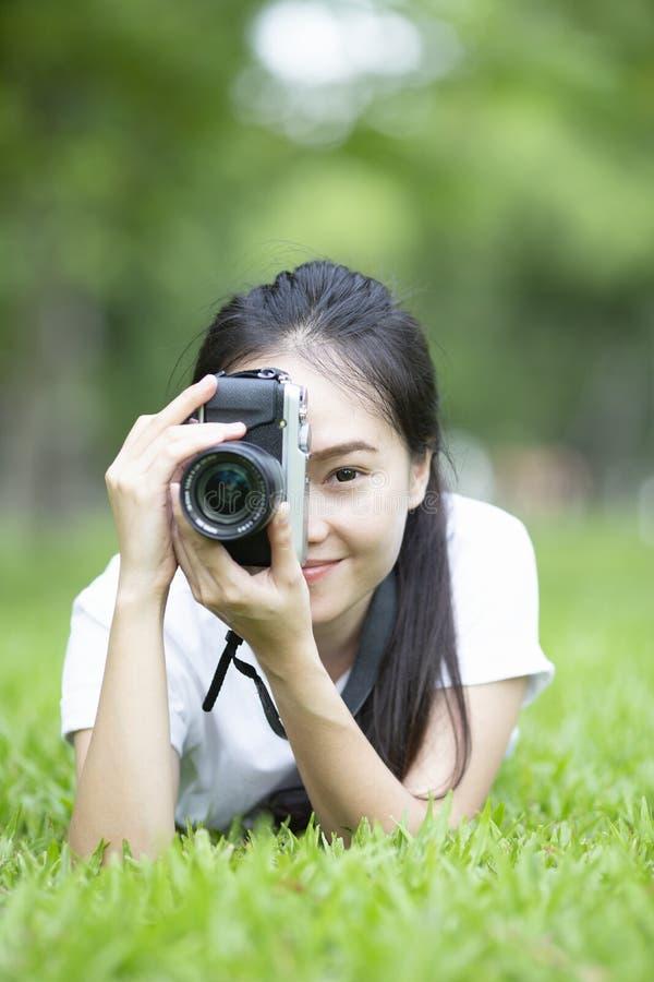 拍与减速火箭的照相机的妇女或女孩摄影师照片在草躺下 免版税库存图片