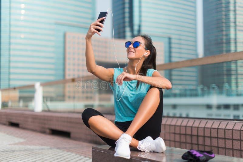 拍与她的智能手机的年轻健身妇女照片,休息在行使或跑以后外面在城市 免版税库存图片