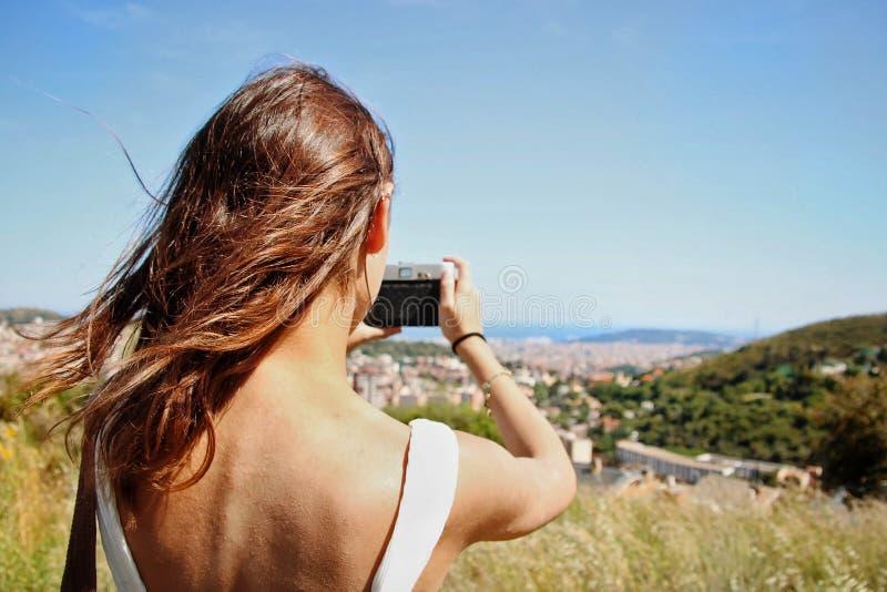 拍与她的照相机的女孩一张照片 免版税库存照片