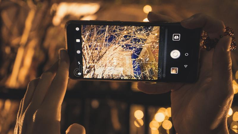 拍与她的电话的少女一张照片对餐馆在晚上 库存图片