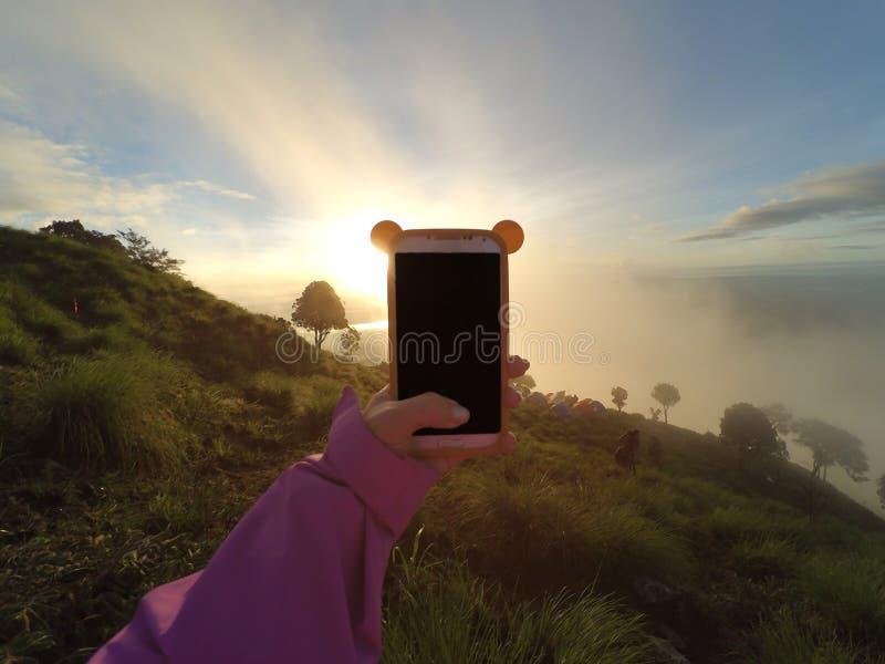 拍与巧妙的电话的手照片在山峰 日出轻的口气 免版税库存照片