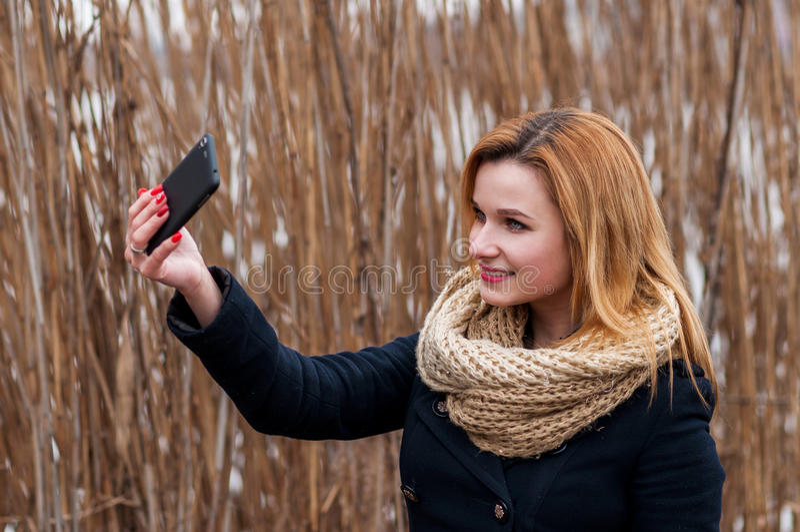 拍与巧妙的电话的美丽的少妇特写镜头一张selfie照片户外 免版税库存图片