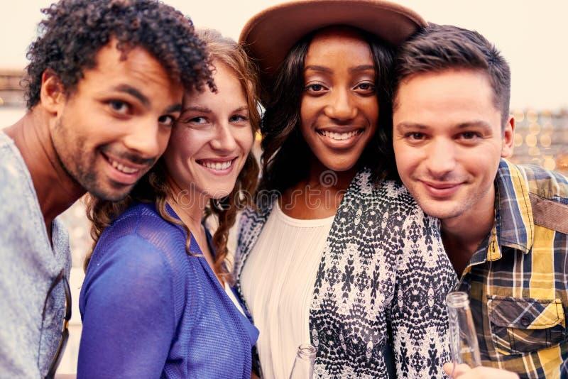 拍与手机的不同种族的millenial小组朋友一张selfie照片在屋顶terrasse在日落 库存照片